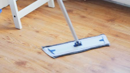 swabber : people, housework and housekeeping concept - woman with mop cleaning floor at home Stock Footage