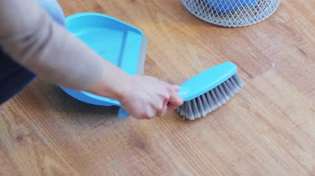 temizleme maddesi : people, housework and housekeeping concept - woman with dustpan and brush sweeping floor at home