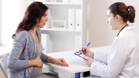 gynaecology : pregnancy, gynecology, medicine, health care and people concept - gynecologist doctor with clipboard and pregnant woman meeting at hospital Stock Footage