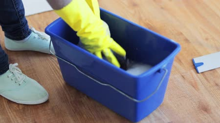 swabber : people, cleaning, housework and housekeeping concept - woman washing and squeezing mop rag in bucket at home