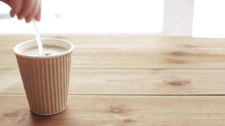 elvihető : unhealthy eating and drinks concept - hand adding and stirring sugar in disposable cup of coffee and covering it with plastic lid on wooden table