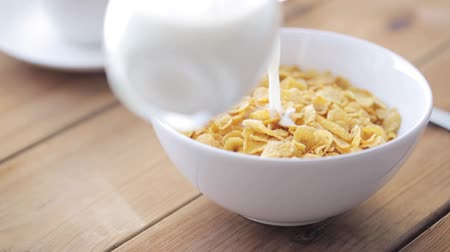 cereais : breakfast, food, objects and eating concept - milk pouring to corn flakes ball on wooden table Vídeos