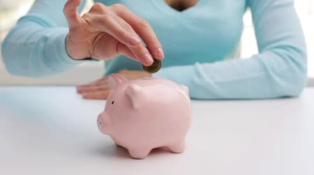 валюта : business, finance, saving, banking and people concept - woman putting one euro coin into piggy bank