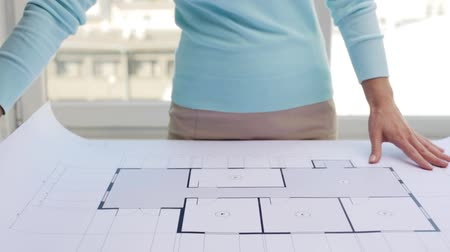 business, architecture, building, construction and people concept - woman unwrapping architectural blueprint Stock Footage