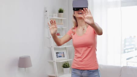 онлайн : technology, cyberspace, entertainment, gaming and people concept - happy young woman with virtual reality headset or 3d glasses playing game at home