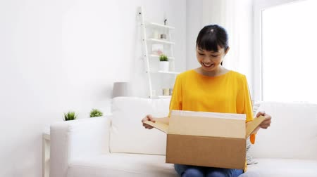 tektura : people, delivery, commerce, shipping and shopping concept - happy asian young woman taking jeans out of cardboard parcel box at home