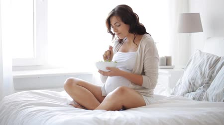 comer : pregnancy, healthy eating, food and people concept - happy pregnant woman eating salad in bed at home