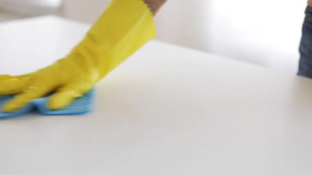 temizleme maddesi : people, housework and housekeeping concept - hand in rubber glove applying cleanser to rag and cleaning coffee stain on table Stok Video