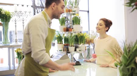 flower shops : people, shopping, sale, floristry and consumerism concept - happy florist man giving flowers to woman at flower shop Stock Footage