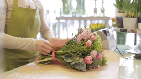 floral composition : people, shopping, sale, floristry and consumerism concept - happy florist woman wrapping flowers in paper and giving them to man at flower shop