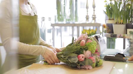 flower shops : people, shopping, sale, floristry and consumerism concept - happy florist woman counting bunch cost at cashbox and man with credit card paying for purchase at flower shop Stock Footage