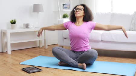 artı : fitness, sport, yoga, training and people concept - happy african woman in lotus pose exercising on mat at home Stok Video
