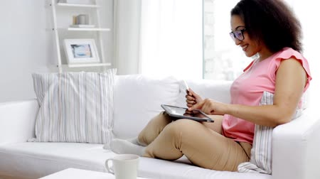bancos : people, internet bank, online shopping, technology and e-money concept - happy african american young woman sitting on sofa with tablet pc computer and credit card etrering bank code at home