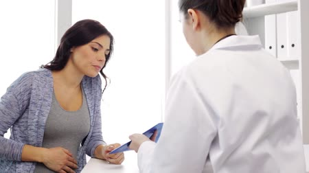 maternity hospital : pregnancy, gynecology, medicine, health care and people concept - gynecologist doctor with clipboard and pregnant woman meeting at hospital Stock Footage