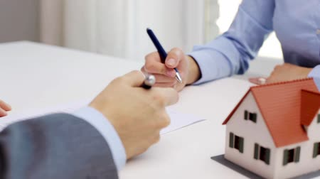 dom : business, real estate, deal and people concept - man and woman with house model and pen signing contract document and shaking hands at office