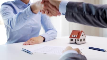 real : business, real estate, deal and people concept - man giving house keys to woman and shaking hands at office Stock Footage