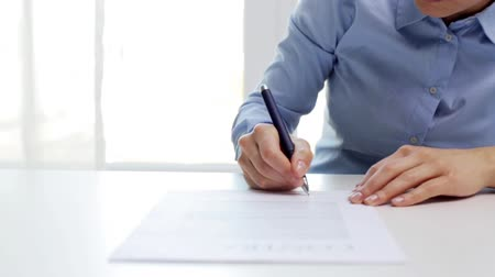 smlouva : architecture, building, business, real estate and people concept - woman with house model and pen signing contract document at office