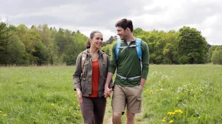 hiking : travel, hiking, backpacking, tourism and people concept - happy couple with backpacks holding hands and walking outdoors Stock Footage