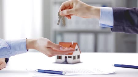 real : business, real estate, deal and people concept - man giving house keys to woman at office at office Stock Footage
