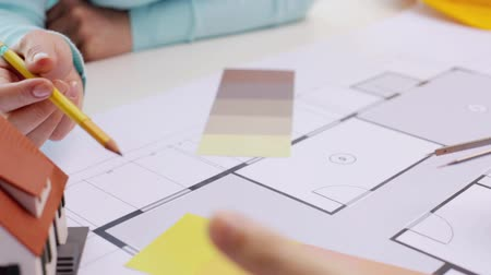 swatches : architecture, building, construction, real estate and people concept - woman and male architect with compass and scale ruler discussing blueprint of living house at home or office Stock Footage