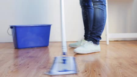 temizleme maddesi : people, housework and housekeeping concept - woman with mop cleaning floor at home Stok Video