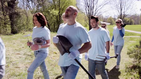 wolontariat : volunteering, charity, people and ecology concept - group of happy volunteers with tree seedlings and gardening tools walking in park