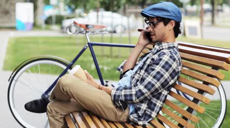 espetáculos : leisure, technology, communication and people concept - smiling man calling on smartphone sitting on city street bench with coffee cup over fixed gear bicycle