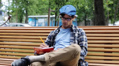 inspiração : lifestyle, creativity, art, inspiration and people concept - creative man or artist with pencil and sketchbook drawing something sitting on city street bench