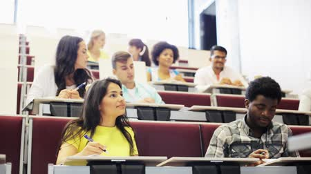 mezinárodní : education, high school, university, learning and people concept - group of international students with notebooks sitting in lecture hall and talking