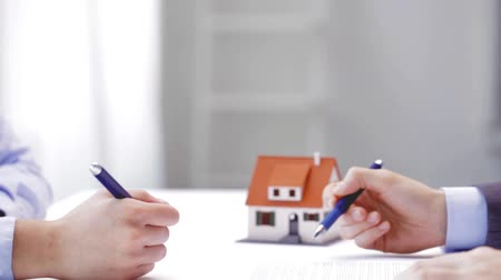 tratar : business, real estate, deal and people concept - man and woman with house model and pen signing contract document and shaking hands at office