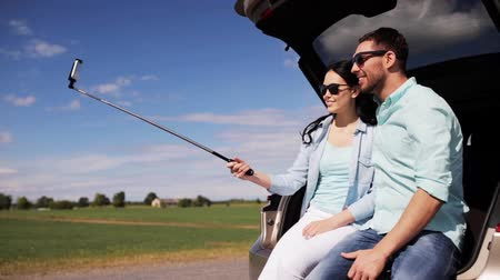 vara : technology, travel, vacation, road trip and people concept - happy couple with smartphone selfie stick sitting on trunk of hatchback car outdoors and taking picture