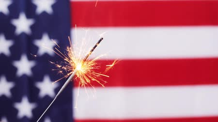 american independence day, patriotism, holidays and celebration concept - close up of sparkler burning over american flag Stock Footage