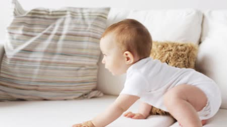 kiddy : childhood, babyhood and people concept - happy little baby crawling along sofa at home