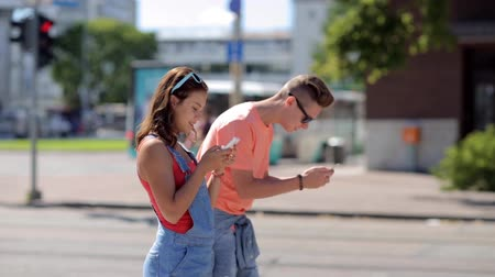realidade : happy teenage couple with smartphones in city Vídeos
