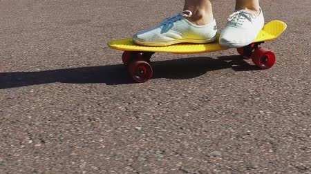 deskorolka : teenage girl feet riding short modern skateboard