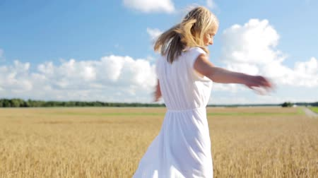 вокруг : smiling young woman in white dress on cereal field Стоковые видеозаписи