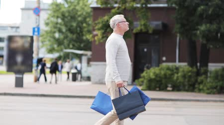 transportar : senior man with shopping bags walking in city Stock Footage