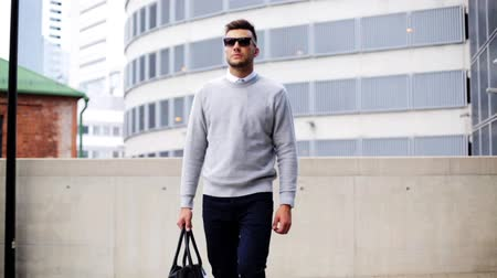 tonları : young man with sunglasses and bag walking in city