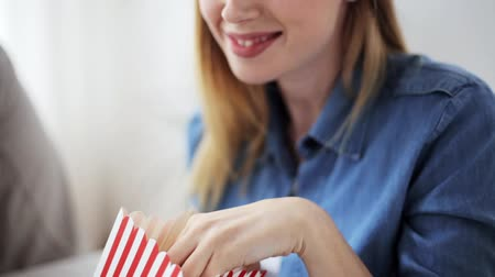 попкорн : happy woman eating popcorn and watching tv at home