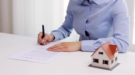 properties : woman with house model and pen signing contract Stock Footage