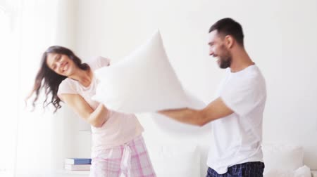 poduszka : happy couple having pillow fight in bed at home Wideo