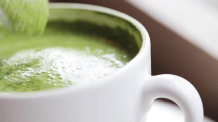 teaspoon stirring matcha green tea latte in cup