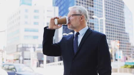 coffee time : senior businessman drinking coffee on city street