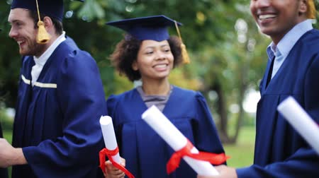 promoce : happy students in mortar boards with diplomas