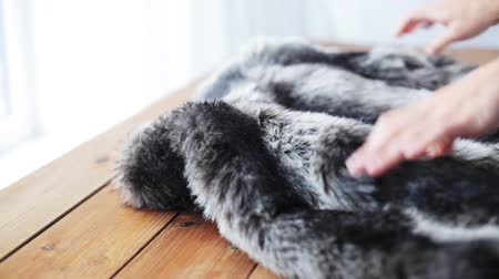 домохозяйка : woman folding faux fur jacket on table at home Стоковые видеозаписи