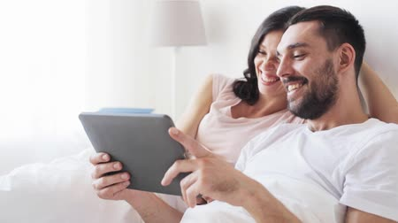 латинский : smiling couple in bed with tablet pc computer Стоковые видеозаписи