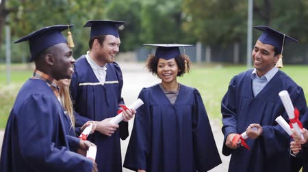 habarcs : happy students in mortar boards with diplomas