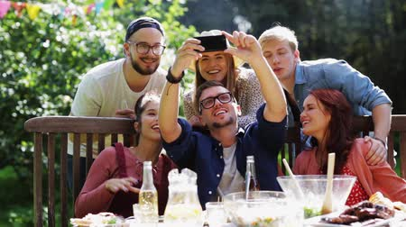 képek : friends taking selfie at party in summer garden Stock mozgókép