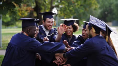 sucesso : happy students in mortar boards with hands on top