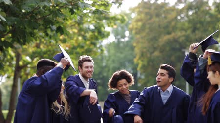 promoce : happy students throwing mortar boards up